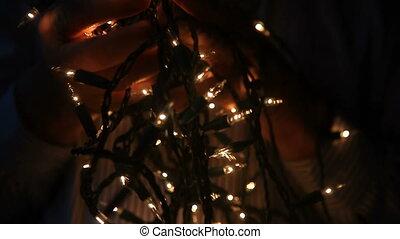 man untangling Christmas lights