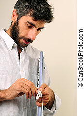 Man Untying Cable Of The Keyboard