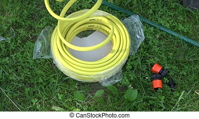 Man unwinding yellow watering hose