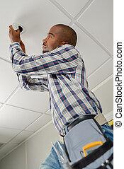Man up a ladder in an office