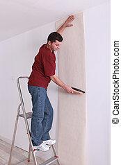 man upholstering a wall