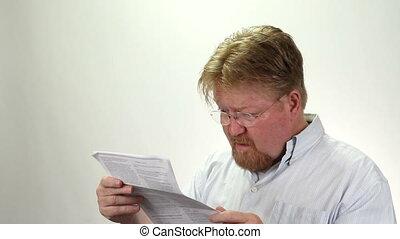 Man Upset About Bills Debts - Man looking at his bills and...
