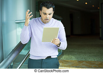 Man upset by what he sees on tablet - Closeup portrait, very...