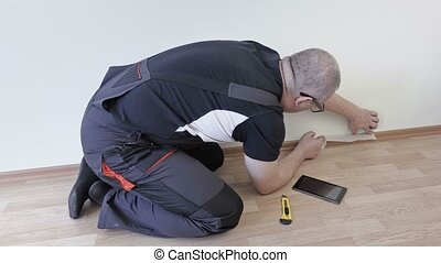 Man use adhesive tape on the floor to the wall