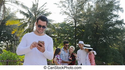 Man Use Cell Smart Phone Chatting Online Over Young People Group In Tropical Palm Tree Park