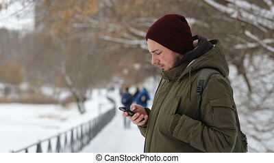 Man use cellphone in the park at winter