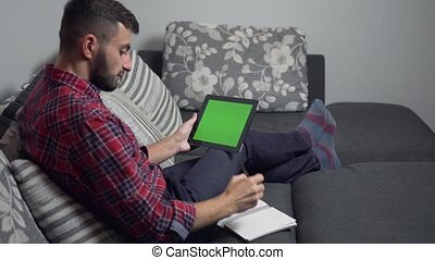 Man Use Tablet PC with Green Screen and Notebook