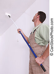 Man user roller extension to paint the ceiling