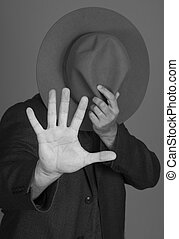 Shy man hides face with hat