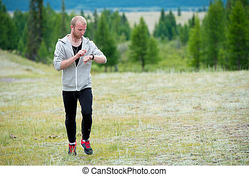Man uses a smart watch during the run in the mountains.