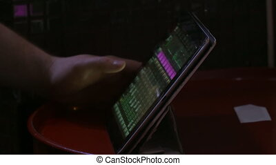 Man uses a tablet in a dark room touching his fingers - A...