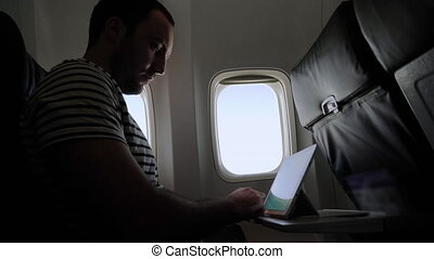 Man uses a tablet in a passenger plane. Professional shot in 4K resolution. 040. You can use it e.g. in your commercial video, medical, business, presentation, broadcast