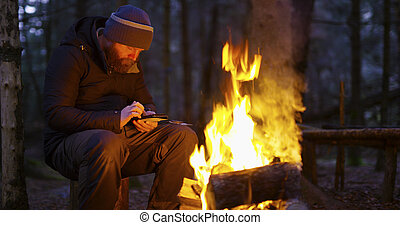 Man uses compass and smart phone by camp fire
