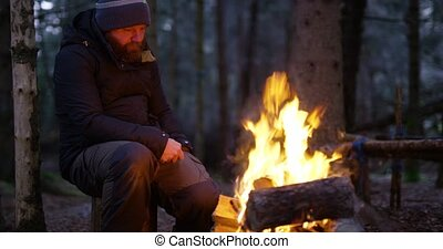 Man uses compass and smart phone by campfire in the forest -...