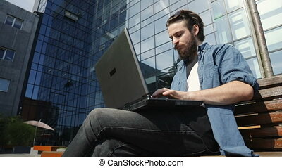 Man Uses Laptop Outdoors - Focused intelligent man using...