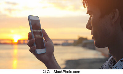 Man uses smart phone at beautiful sunset on the beach