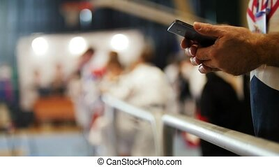 Man uses smartphone at sport competitions of karate, close...