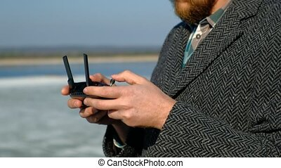 man uses the remote control for the drone - a man with a...