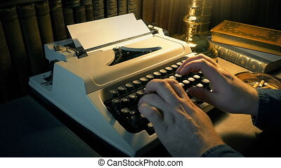 Man using typewriter in a dark room with desk lamp and rows of books