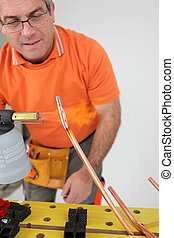 Man using a blowtorch on copper pipe
