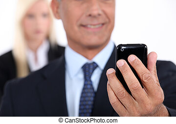 Man using a cellphone with his assistant in the background