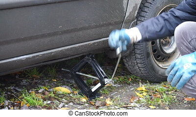 Man using a jack for putting car down - Changing a car...