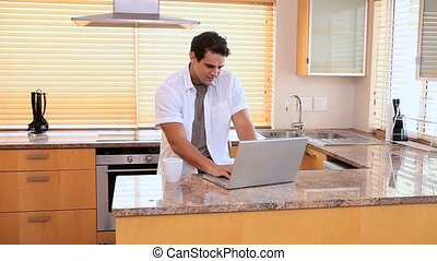 Man using a laptop and drinking a coffee