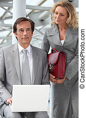 Man using a laptop computer accompanied by a woman with a red briefcase
