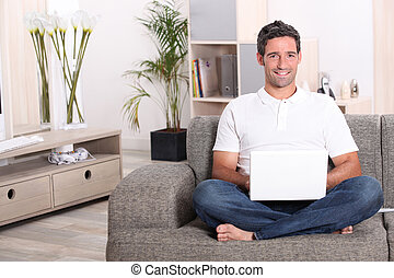 Man using a laptop computer in his front room
