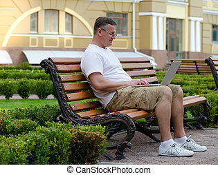 Man using a laptop on a public bench