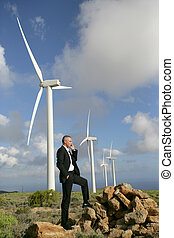 Man using a mobile phone next to wind turbines