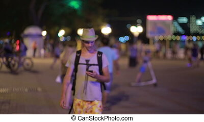 man using a mobile phone on the street. a handsome man in a hat with smartphone