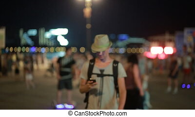man using a mobile phone on the street. a handsome man in a hat with smatrtfonom