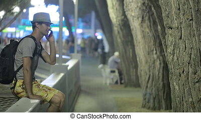 man using a mobile phone on the street. a handsome man in a hat with smatrtphone