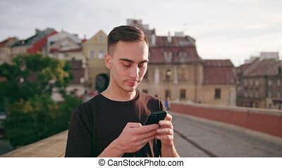 Man Using a Phone in Town - A young man using a phone in the...