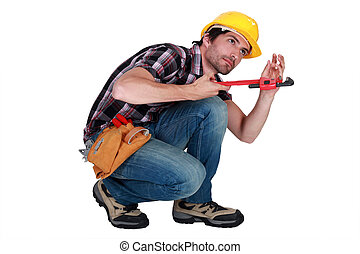 Man using a pipe wrench to tighten a pipe