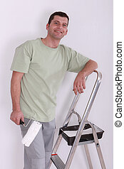 Man using a roller to paint a room white