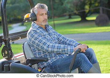 man using a sit in lawn mower