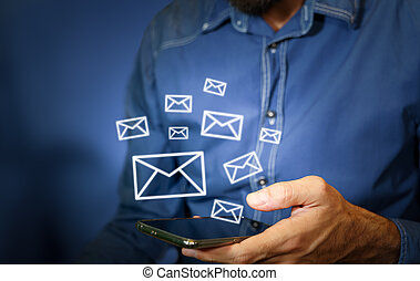 Man using a smartphone with email icons being sent out.