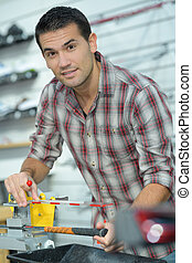 man using a steel cutter machine in factory
