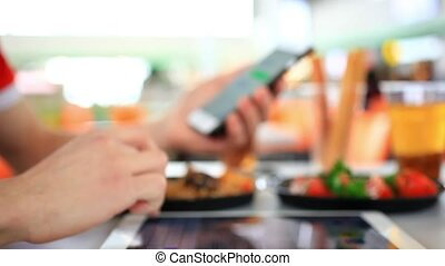 Man using a Tablet Pc and send message on phone in cafe terrace, some food. Close up change focus. HD. 1920x1080