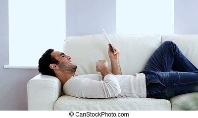 Man using a tablet pc on the couch