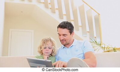 Man using a tablet while his son is watching