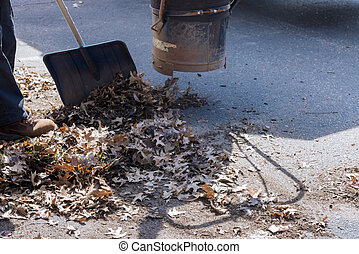 Man using a vacuum cleaner works in an autumn road, off leaves fallen