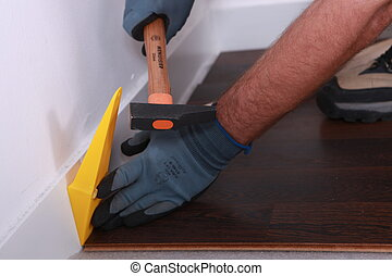 Man using a wedge to lay wooden flooring