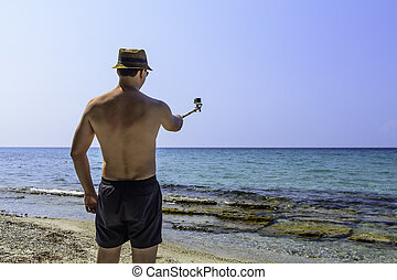 Man using an action camera on the beach over ocean background