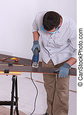 Man using an electric jigsaw to cut a piece of wooden flooring