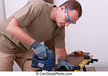 Man using an electric saw to cut a wooden floorboard