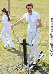 Man using an elliptical machine in an outdoor gym