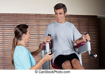 Man Using An Exercise Machine While Looking At Instructor
